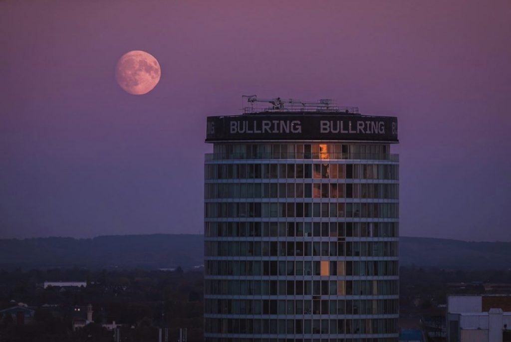 Top of rotunda serviced apartments with moon behind it with a purple sky