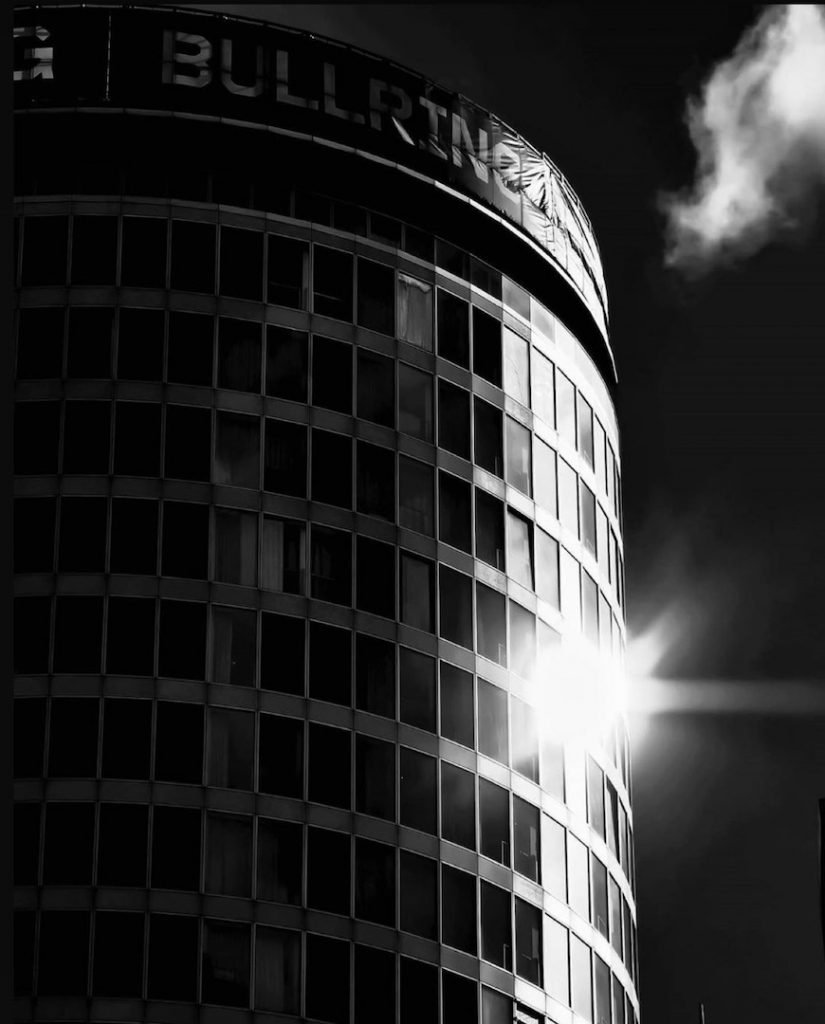 Staying Cool's Rotunda aparthotel exterior in black and white with sun reflecting off a window taken by photographer @_shamrock_sean