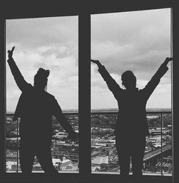 Black an white picture of guests posing in a staying cool serviced apartment at rotunda birmingham with city views behind them