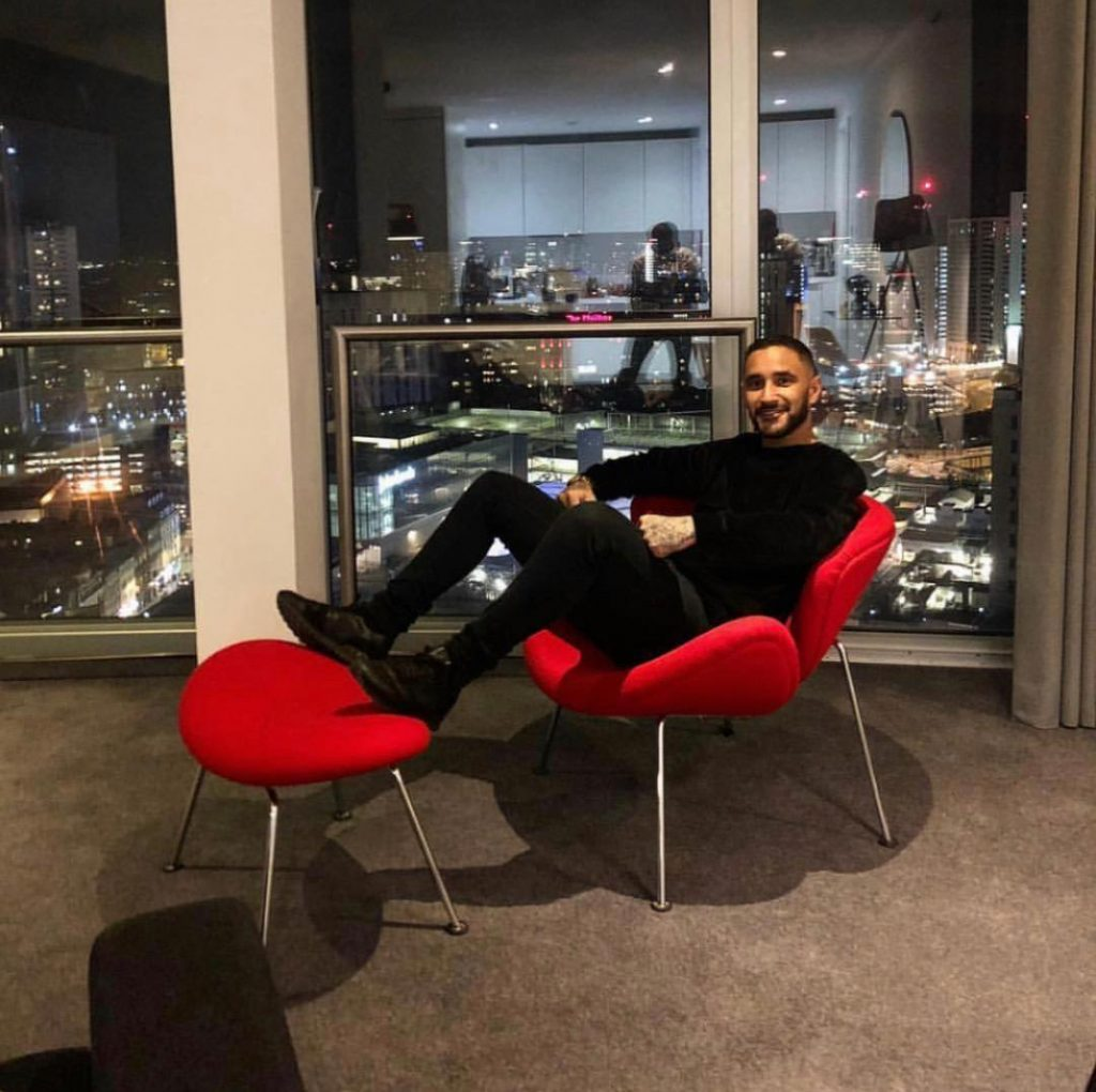 A guest sat in the red chair in a Clubman serviced apartment in Birmingham