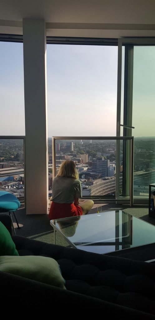 Guest sat by the window at staying cool's rotunda apart hotel enjoying the city views of Birmingham