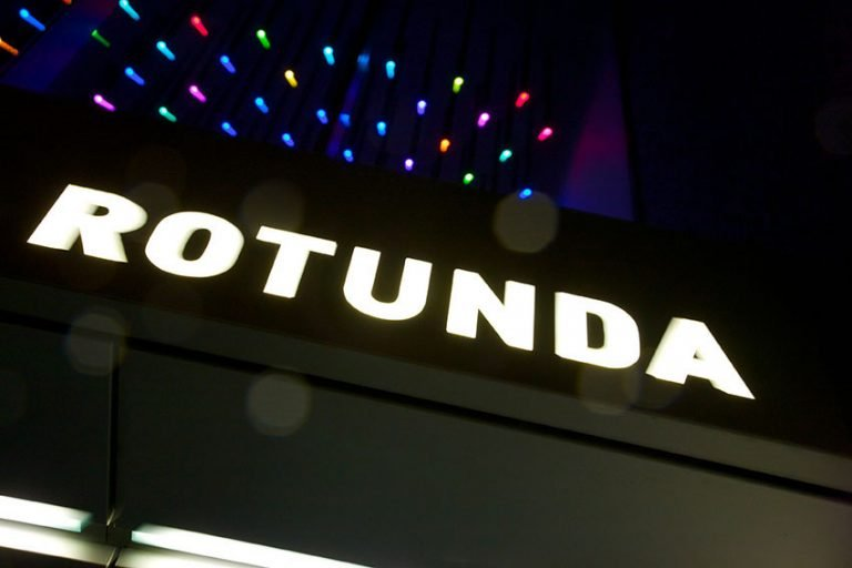 Rotunda Aparthotel entrance with signage above the door at night
