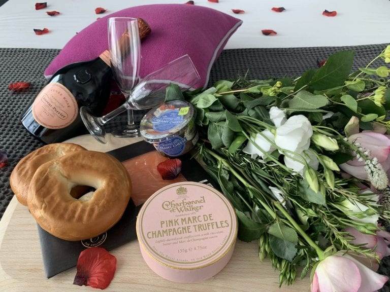 Champagne, salmon bagels and chocolate truffles with flowers
