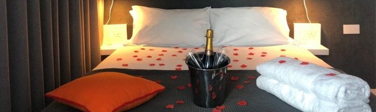 Romantic bedroom showing rose petals scattered across the bed plus a bottle of Champagne on ice