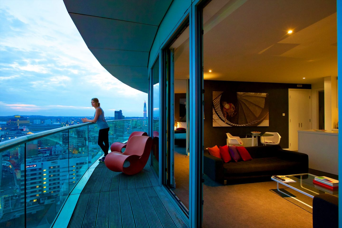 Guest admiring the city view on a Staying Cool penthouse balcony