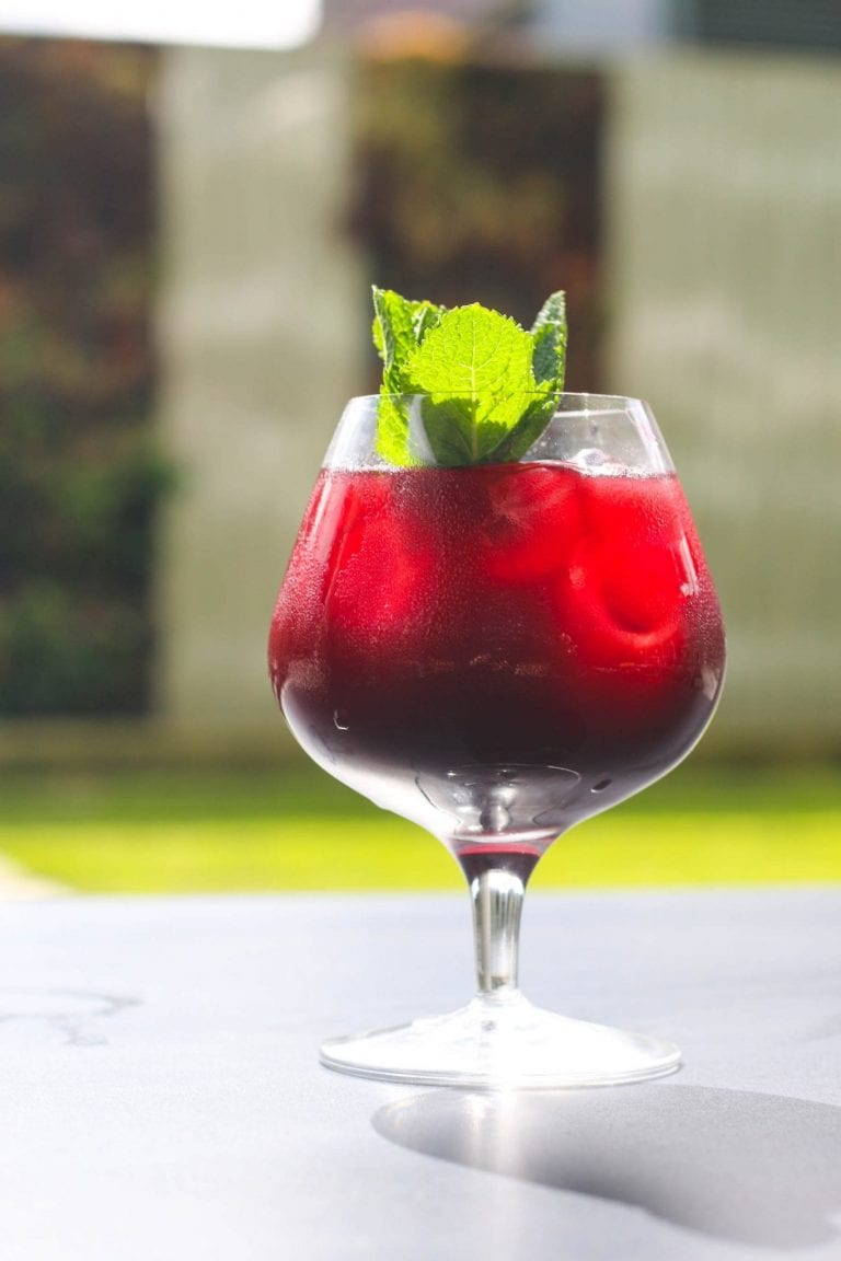 Classic raspberry cocktail in a glass with a sprig of mint on a bar