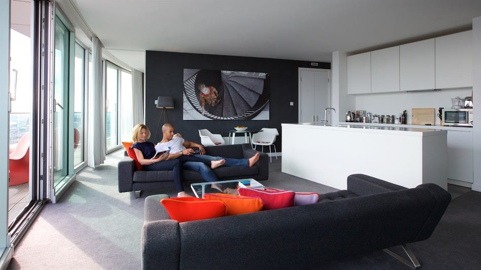 Couple relaxing on sofa in penthouse apartment