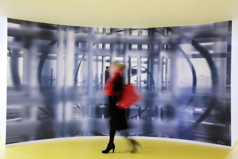 Woman with red bag walking across one of the lobbies in the Rotunda. It has a bright yellow floor and a huge black and white photograph on the wall.