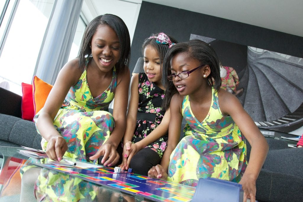 Three girls playing board game at Staying Cool