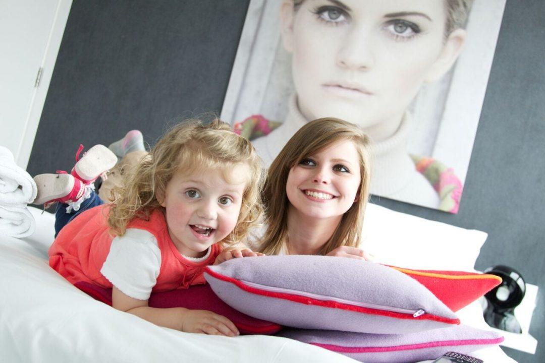 Two girls on a bed enjoying a family-friendly break.