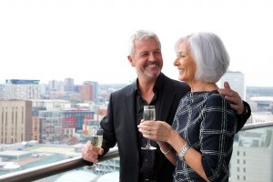 couple enjoying the view with champagne on staying cool's birmingham aparthotel balcony