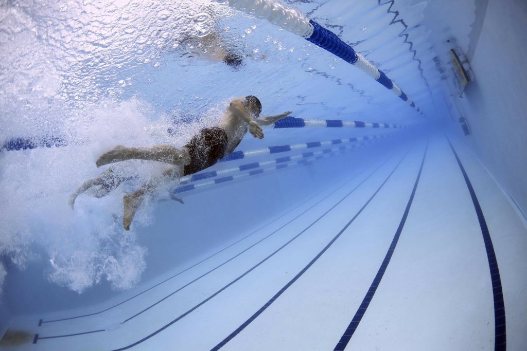Importance of keeping up routine on business travel. Image of swimmers in pool