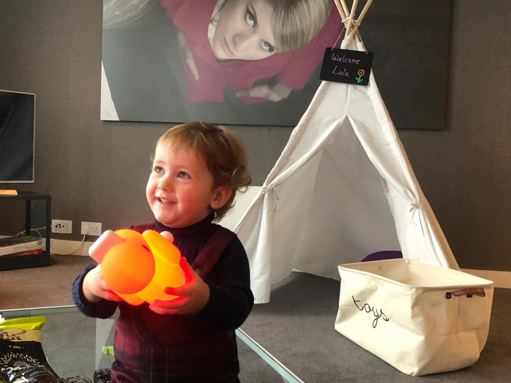 Eco tourism. Toddler smiling whilst enjoying playing with a toy duck and a little tipi in an apartment at Staying Cool at the Rotunda