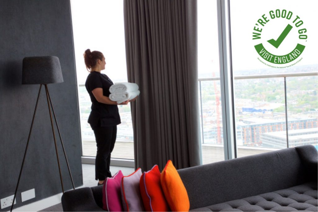 Housekeeper in Staying Cool ApartHotel penthouse lounge looking out at the view