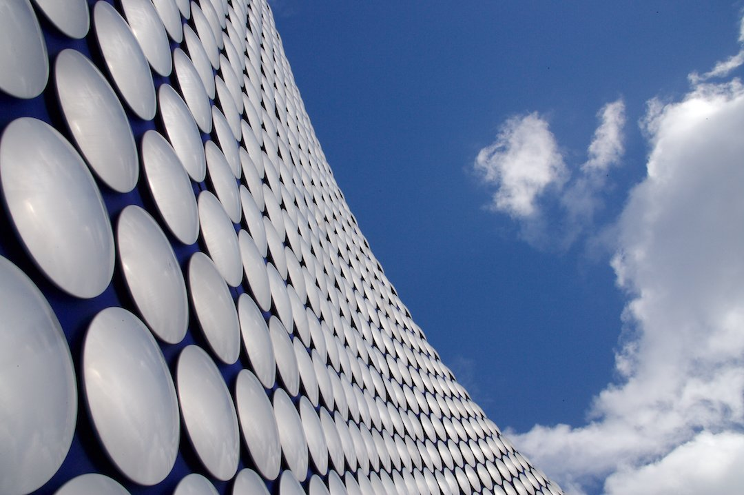 Exterior of Selfridges Birmingham store with blue sky and clouds