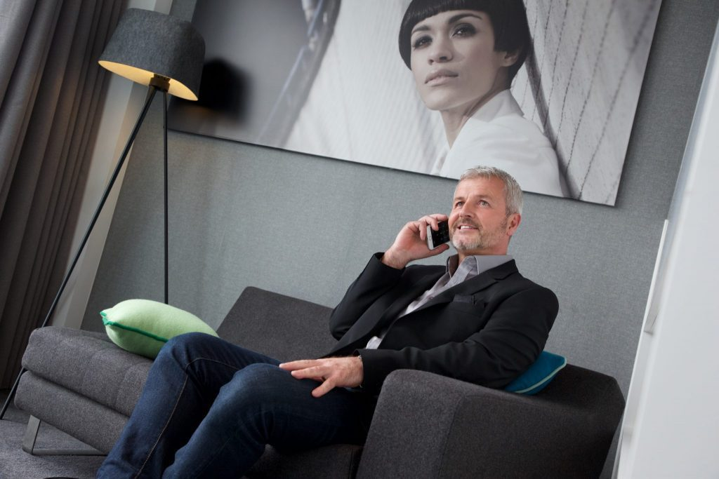 Man on business travel sitting on charcoal sofa in serviced apartment