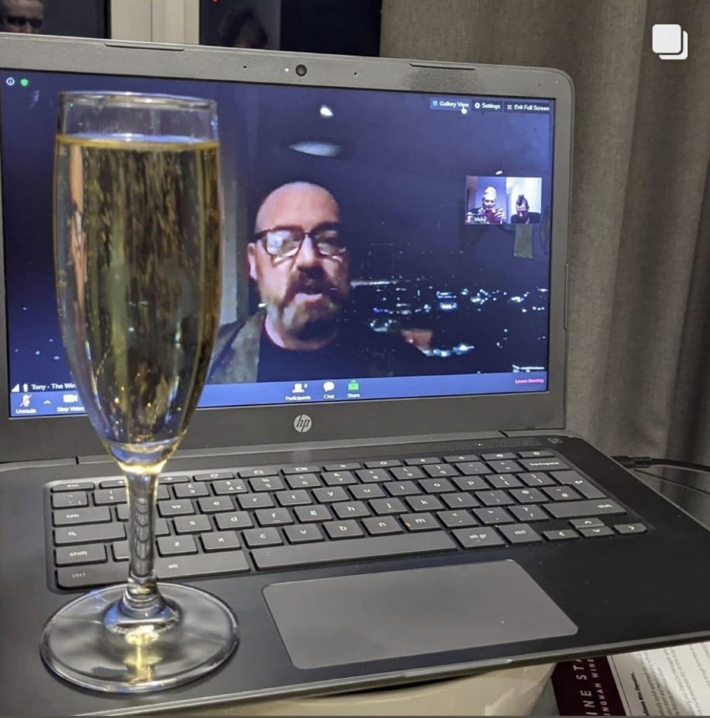 Glass of champagne in front of zoom call with Tony Elvin on screen presenting The Wine Staycation event at Staying Cool's Rotunda Aparthotel