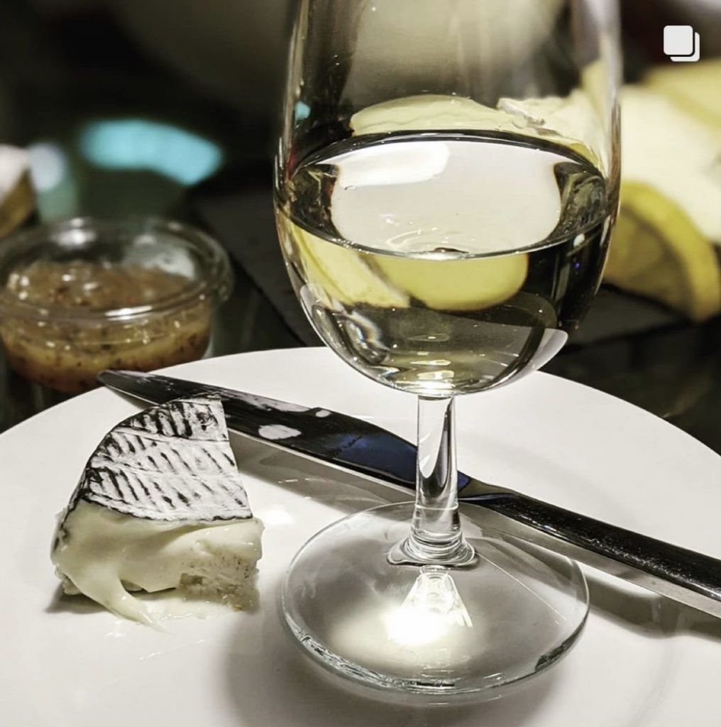 Glass of white wine and smoked cheese on a plate at The Wine Staycation event at Staying Cool's Rotunda Aparthotel