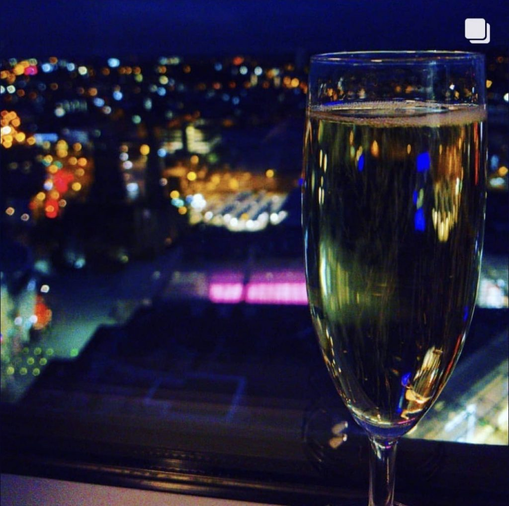 Glass of champagne with Birmingham city lights in the background taken from Staying Cool's Rotunda Aparthotel