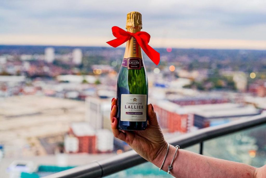Bottle of Lallier Champagne with city views taken from Staying Cool's Rotunda Aparthotel penthouse balcony.