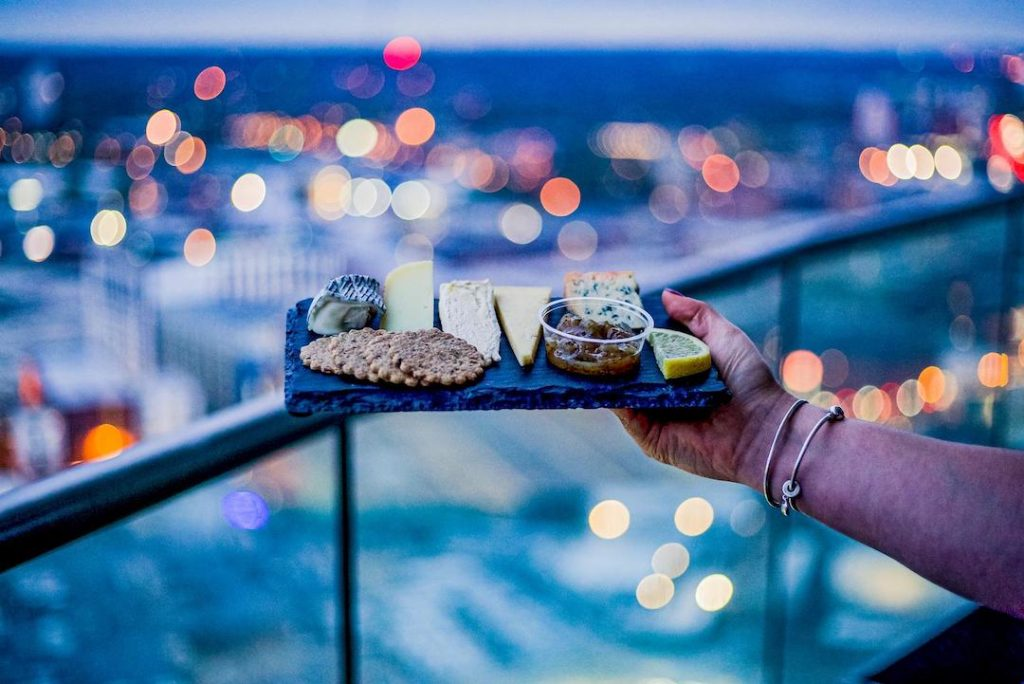 Cheese board selection with city lights in the background at Staying Cool's Rotunda Aparthotel