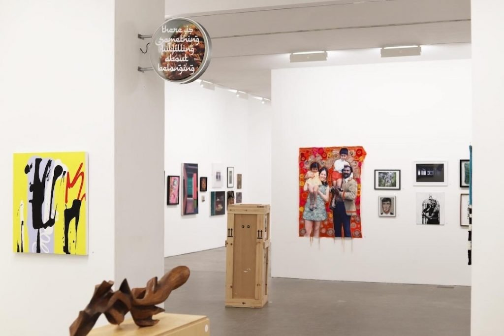 The interior of Birmingham's Ikon Gallery at Brindlayplace with artwork on the walls and a sculpture in the forefront.