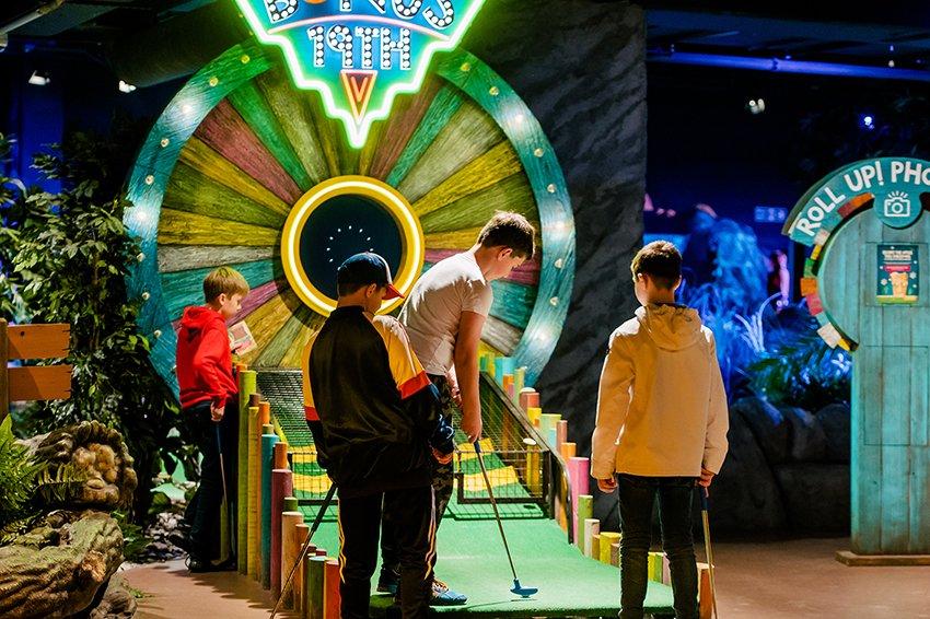 Children plaing miniature golf inside the Treetop Adventure Golf complex.