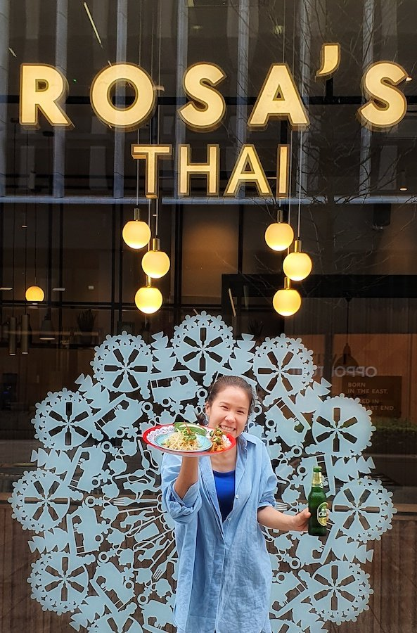 A member of the Rosa's Thai Cafe team standing outside one of their beautiful venues with thai food and a beer in hand.