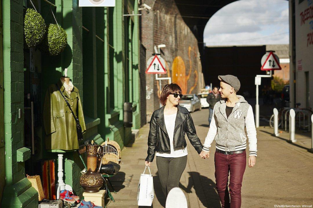 Couple holding hands walking down street outside of the Custard Factory in Digbeth Birmingham