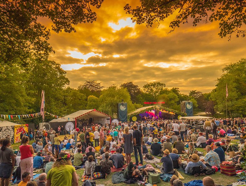 The crowd at Moseley Folk Festival enjoying a live performance at sunset in Moseley Park Birmingham