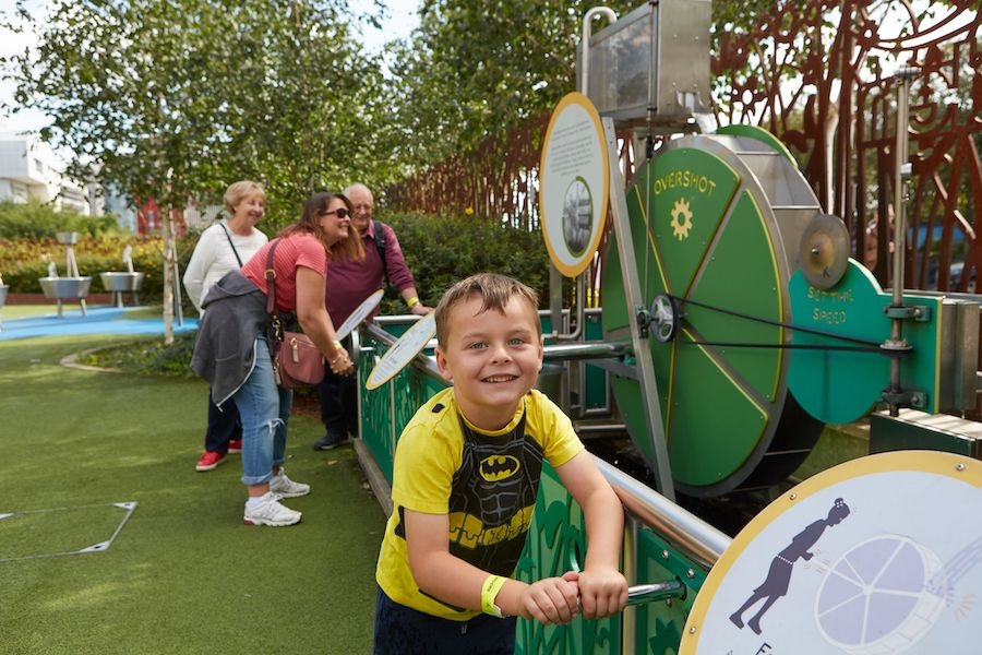 A child playing in ThinkTank Birmingham's Science Garden with family.